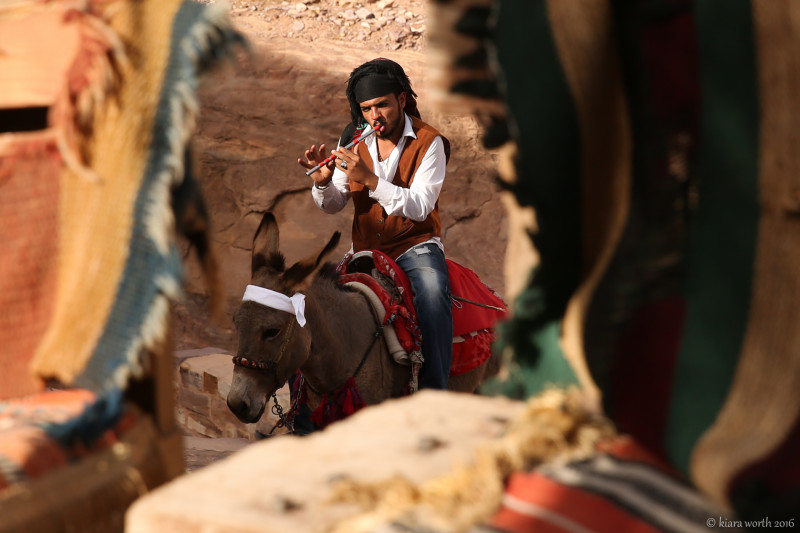 A young man plays the flute while riding a donkey to the Monastery.