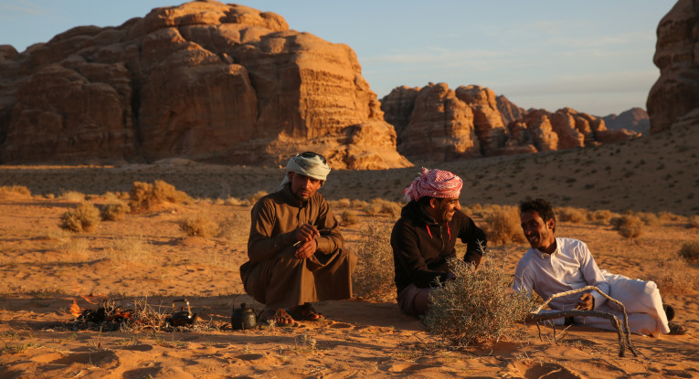Three Bedouin guides prepare hot tea in the setting sun.