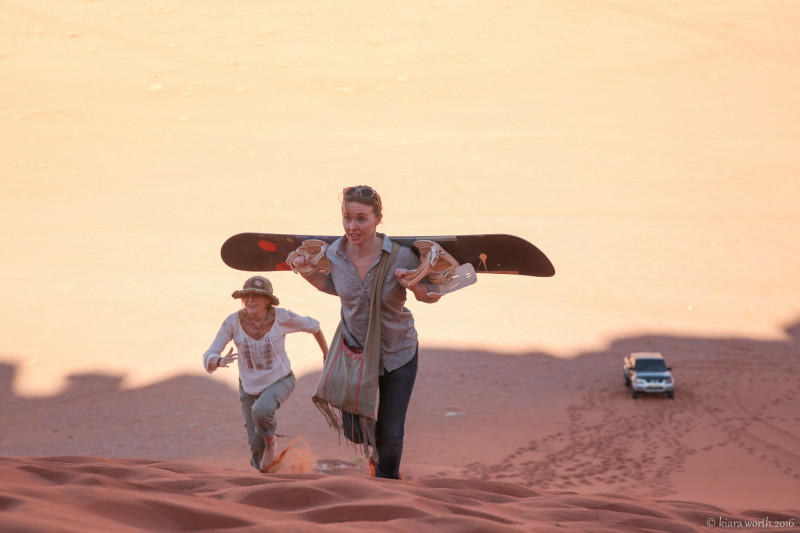 Dune surfing down the red sand dune of Wadi Rum